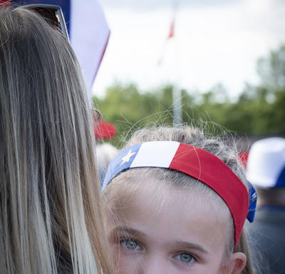 A young girl dressed in Acadian national colours is in her mother's arms.