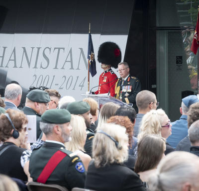 The Chief of the Defence Staff delivers remarks at a podium, two ceremonial guards standing solemnly on either side.
