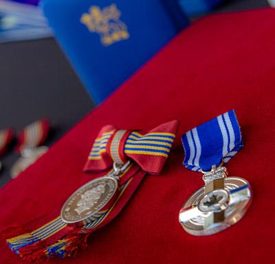 A photo of a Sovereign's Medal for Volunteers and a Meritorious Service Medal.