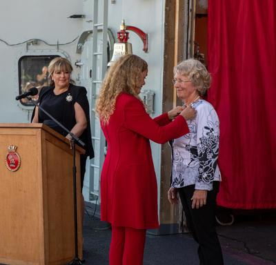 The Governor General pins a medal on a recipient.
