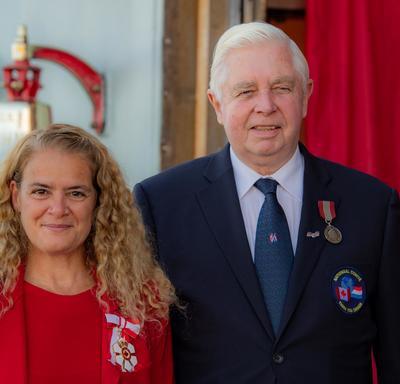 La gouverneure générale prend une photo avec un récipiendaire de médaille.