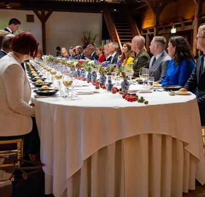 La gouverneure générale est assise parmi les invités à une longue table lors d'un dîner offert par le premier ministre Rutte.