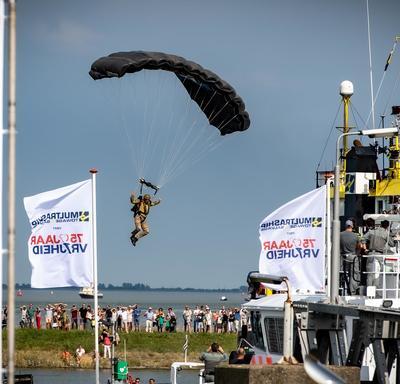 Un parachutiste se prépare à atterrir pendant la cérémonie commémorative à Terneuzen.