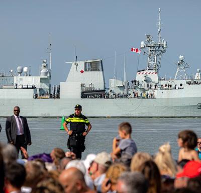 Une photo de la foule qui assistait à la cérémonie commémorative à Terneuzen, une frégate militaire à l'arrière-plan.