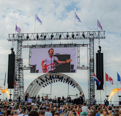 A photo of the main outdoor stage at the commemorative ceremony in Terneuzen, a large crowd surrounds it.