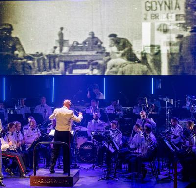 A photo of an orchestra on stage at the commemorative ceremony in the Scheldetheatre in Terneuzen, with footage of the Second World War playing on a large screen.