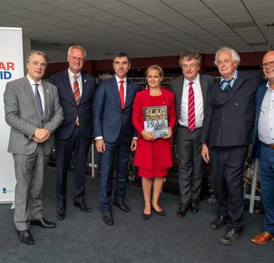 Une photo de la gouverneure générale aux côtés d'une équipe qui a travaillé et publié la première édition d'un livre sur la bataille de l'Escaut.