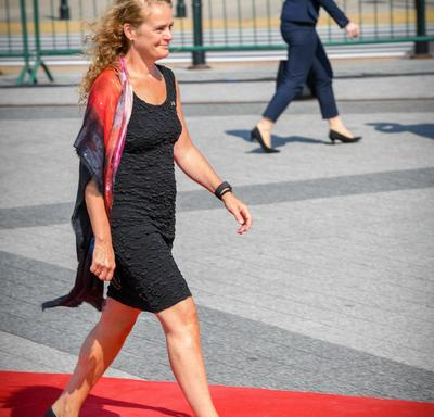 The Governor General walks along a red carpet towards her seat at the commemorative ceremony.