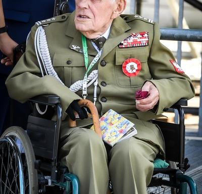 A photo of a Polish veteran in a wheelchair at the commemorative ceremony.