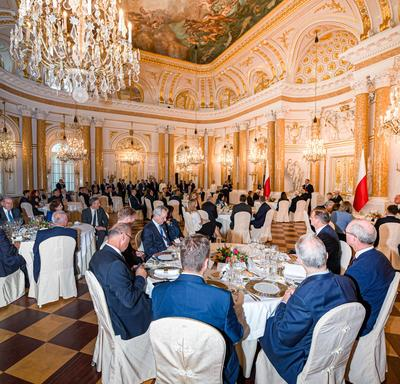 A photo of the Heads of State sitting at tables inside the Royal Castle in Warsaw.