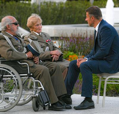 A photo of a man in a suit speaking with two Polish veterans in wheelchairs.