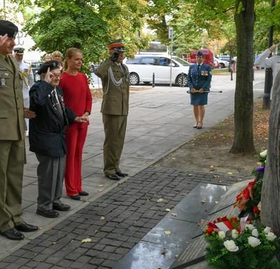 Two Polish officers and a Polish veteran salute a monument alongside the Governor General.