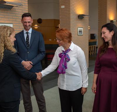 La gouverneure générale serre la main d'un employé de l'Organisation pour l'interdiction des armes chimiques pendant que d'autres employés regardent.