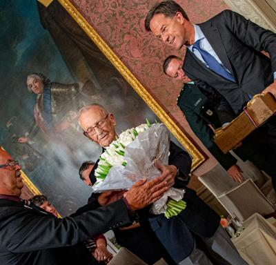 The Prime Minister of the Netherlands hands tulips and a box of bulbs to Canadian veteran Don White.