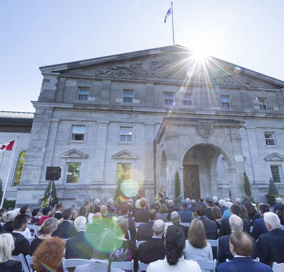 A photo of a crowd seated outside the main entrance to Rideau Hall during an outdoor Order of Canada ceremony.