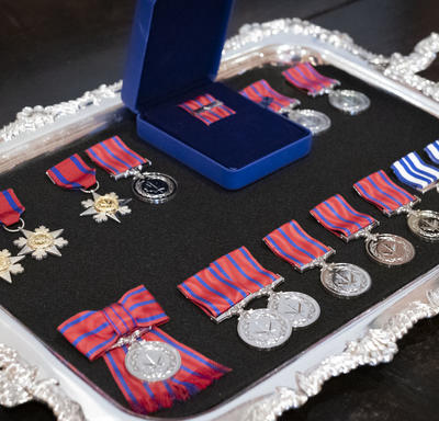 A photo of mixed honours medals, organized on a tray.