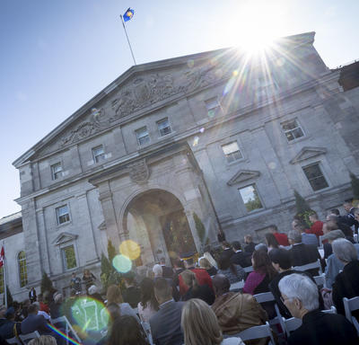 A photo of the front entrance of Rideau Hall, with guests seated for a ceremony.
