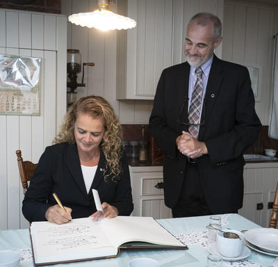 The Governor General signing the guest book at the Maison Alphonse-Desjardins.