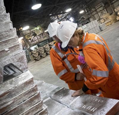 Governor General looking at blocks of zinc.