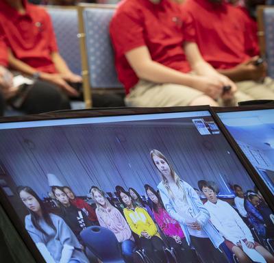 Une photo d'élèves assis dans la salle de la tente de Rideau Hall, avec une salle de classe virtuelle de Vancouver sur un écran.