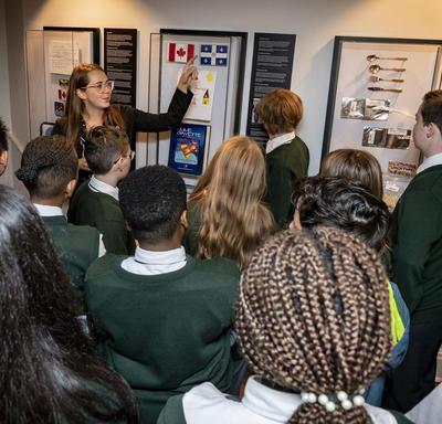 Un employé du bureau du secrétaire de la gouverneure générale présente aux élèves des éléments de l'exposition Oser rêver.