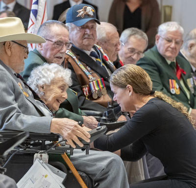 The Governor General kneels down and speaks with a veteran during the launch of the 2019 National Poppy Campaign.