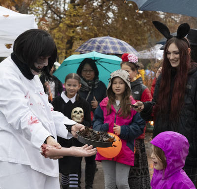 Kids look on as a Rideau Hall staff member holds a Halloween inspired dish.