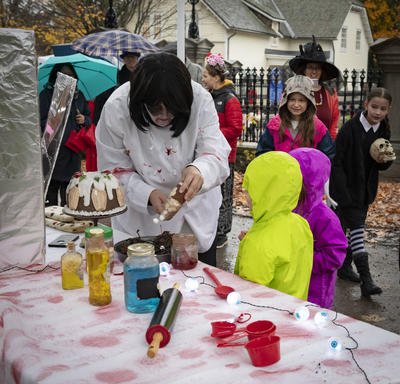 Kids look on as a staff member creates a Halloween food creation.