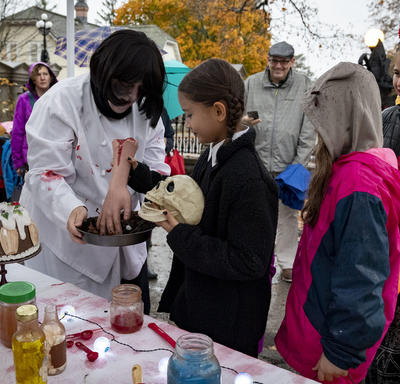 Kids look on as Rideau Hall staff show off ghoulish treats.