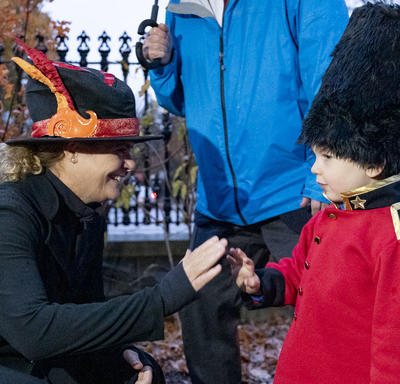 The Govenror General greets a young child dressed as a member of the Royal Canadian Mounted Police.