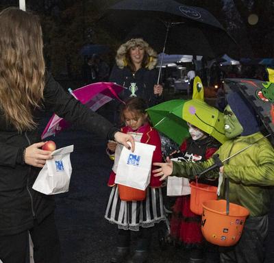 Children receiving Halloween treat bags.