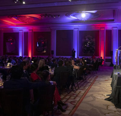 Side view of a room where Governor General Julie Payette is seen, at the far right of the photo, on stage, at a podium. The room is very dark but there are some purple and pink lights.