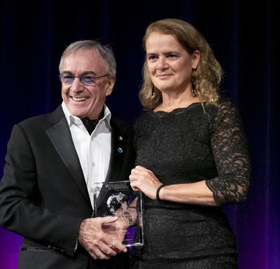 Daniel Lamarre, President of Cirque du Soleil, and Governor General Julie Payette of Canada hold a prize made of transparent glass in their hands.