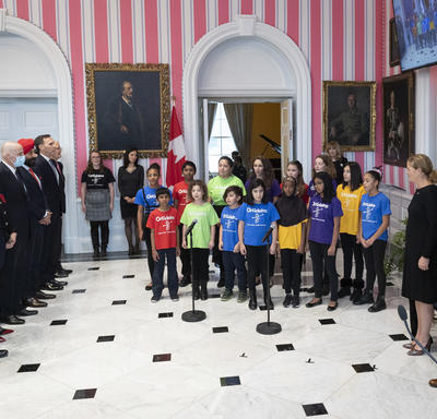 A choir of kids is standing at the front of the room.