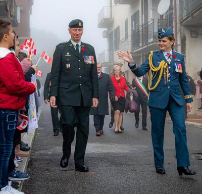 Governor General Julie Payette, wearing the Royal Canadian Air Force uniform, is waving to children holding small Canadian flags. The children are standing on the sidewalk.