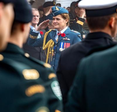 Governer General Julie Payette, wearing the Royal Canadian Air Force uniform, is saluting troops..