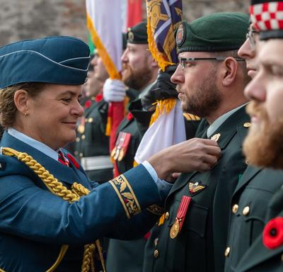 Governor General Julie Payette is adjusting a poppy on the uniform of a member of the Canadian Forces.