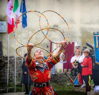Le groupe autochtone canadien Warrior Eagle danse devant le monument Pontecorvo. Une danseuse tient de grands cerceaux.