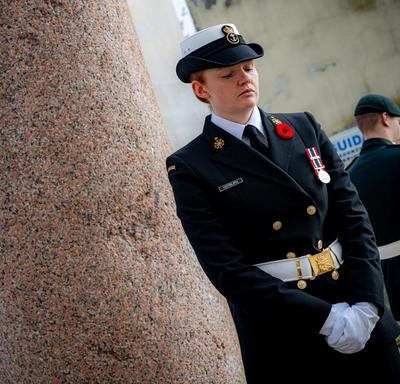 A female member of the Canadian Armed Forces is standing sentry at one corner of the Pontecorvo Monument.