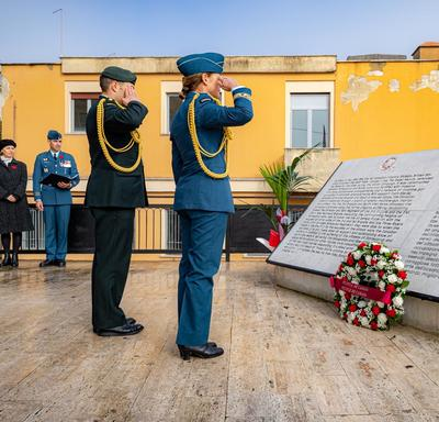 Governor General Julie Payette, wearing the Canadian Air Forces uniform is saluting in front of the Canadian Plaque in Montecorvo.