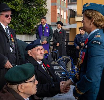 Governor General Julie Payette, wearing the Royal Canadian Air Force uniform, is mingling outside with veterans.