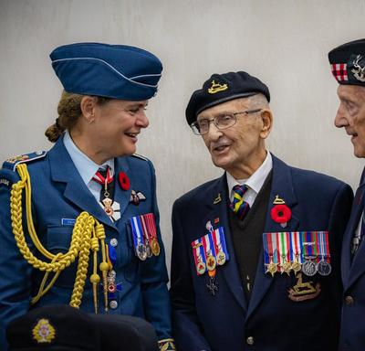 Governor General Julie Payette, wearing the Royal Canadian Air Force uniform, is smiling, talking with veterans.