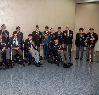 Governor General Julie Payette, wearing the Royal Canadian Air Force uniform, is posing for a photo with veterans.
