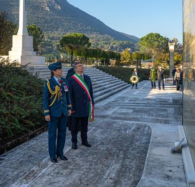 Governor General Julie Payette, wearing the Royal Canadian Air Force uniform, is standing in front of a monument with the mayor of the city, in Cassino.