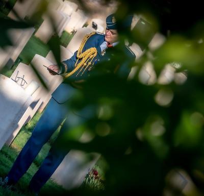 La gouverneure générale Julie Payette, en uniforme des Forces aériennes canadiennes, est vue de loin, à l'ombre d'un arbre, au cimetière de guerre de Cassino.