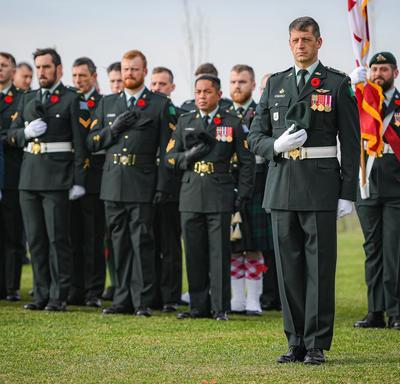 Des membres des Forces armées canadiennes se tiennent debout, la main sur le coeur.