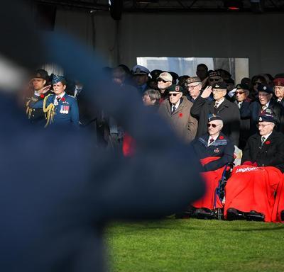 La gouverneure générale se tient aux côtés des anciens combattants et salue.