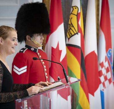 The Governor General delivers remarks at a podium with national flags and a ceremonial guard behind.