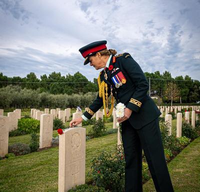 La gouverneure générale dépose une fleur sur une pierre tombale.