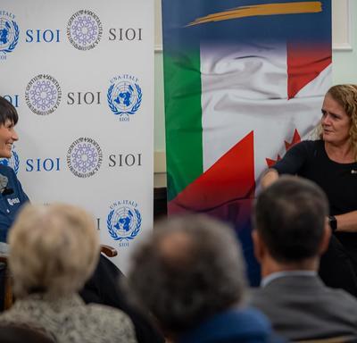 La gouverneure générale est assise sur scène à côtés de l'astronaute italienne Samantha Cristoforetti.
